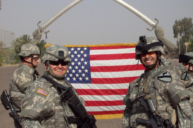 Staff Sgt. Gustavo Sanchez (right), with Forward Support Company D, 4th Squadron, 9th Cavalry Regiment, 2nd Brigade Combat Team, 1st Cavalry Division, pose for a photo after reenlisting in front of the Crossed Sabers in the International Zone on July 4. Sanchez is one of hundreds of Darkhorse Soldiers who have reenlisted during the squadron's 15-month deployment to Iraq.
