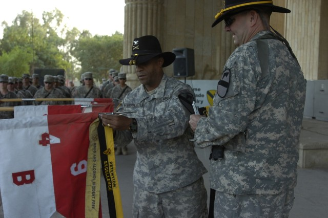 The 2nd Brigade Combat Team, 1st Cavalry Division commander, Col. Bryan Roberts, attaches a retention streamer to the guideon of Troop B, 4th Squadron, 9th Cavalry Regiment during a ceremony at Forward Operating Base Prosperity in central Baghdad Oct. 10.  The squadron was recognized for meeting five retention goals over the last year, while the brigade's top enlisted advisor Command Sgt. Major James Lee looks on.