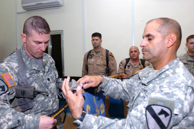 "Las Vegas, Nev., native Lt. Col. Christopher Walach (left), commander of the 1st ""Attack"" Battalion, 227th Aviation Regiment, 1st Air Cavalry Brigade, 1st Cavalry Division, and Bayamon, Puerto Rico, native Command Sgt. Maj. Ismael Medina (right), the senior noncommissioned officer of the battalion, attach a streamer to Company B's guidon for being the top company in reenlistments for the fiscal year during a ceremony at Camp Taji, Iraq, Oct. 10. Muskogee, Okla., native Capt. Chris Morton (center left), the commander of Co. B, recently took command and gave all the credit to his Soldiers and his first sergeant, Bath, Pa., native 1st Sgt. Joseph Wilgeroth, the top noncommissioned officer for the company."
