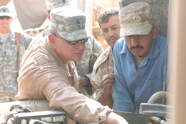 Staff Sgt. Gary Minnich, 26th BSB, 2nd BCT, 3rd Inf. Div., battalion motor sergeant, shows Emhad Abdeohasam, an Iraqi Army mechanic, components of a Humvee engine.at FOB Kalsu Oct. 8.