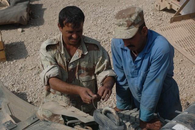 Alaa Hussein, a mechanic warrant officer in the Iraqi Army (left), and Emhad Abdeohasam, an Iraqi Army mechanic, work together to disassemble parts of their Humvee during training by the 26th BSB.