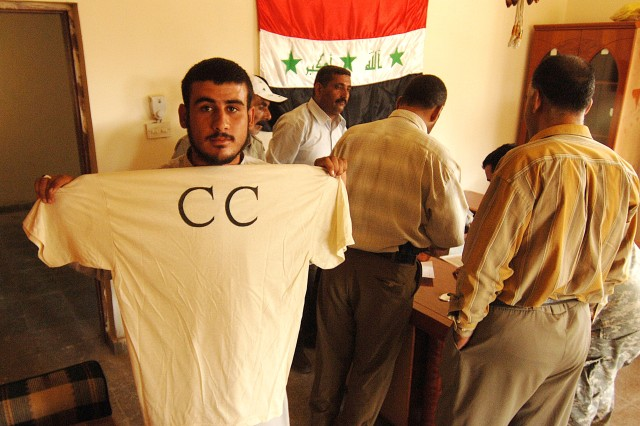 A member of the Concerned Citizens group shows off his new uniform T-shirt after receiving it from 2nd Lt. Kenneth Beasley, 3rd Infantry Division, in Kargulia, Iraq, Oct. 3.