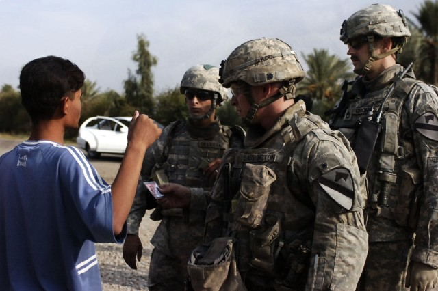 A Baloor resident talks with Soldiers from 6-9 Armored Reconnaissance Squadron, 3rd Brigade Combat Team, 1st Cavalry Division, at a temporary checkpoint after a concerned local citizen stronghold was shot during a drive-by shooting in Baloor, Iraq, Oct. 6.