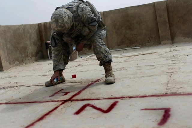 Second Lt. John Barrington of Bravo Troop, 6-9 Armored Reconnaissance Squadron, 3rd Brigade Combat Team, 1st Cavalry Division, paints a marker on a concerned local citizen stronghold in Baloor, Iraq, Oct. 6.