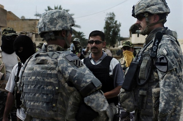 Sgt. First Class Timothy Frank Jr., a platoon sergeant in Bravo Troop, 6-9 Armored Reconnaissance Squadron, 3rd Brigade Combat Team, 1st Cavalry Division, talks with concerned local citizens and a council member about what types of masks are acceptable for CLCs to wear in Baloor, Iraq, Oct. 6.