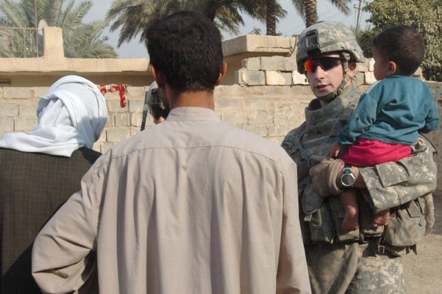 Utopia, Texas native Sgt. Ken Thomas (right), a team leader with Troop C, 1st Squadron, 7th Cavalry Regiment talks with local Iraqi residents near Taji, Iraq during an Oct. 6 foot patrol. Thomas recently received the Silver Star Medal for actions taken in mid-February during an enemy ambush.