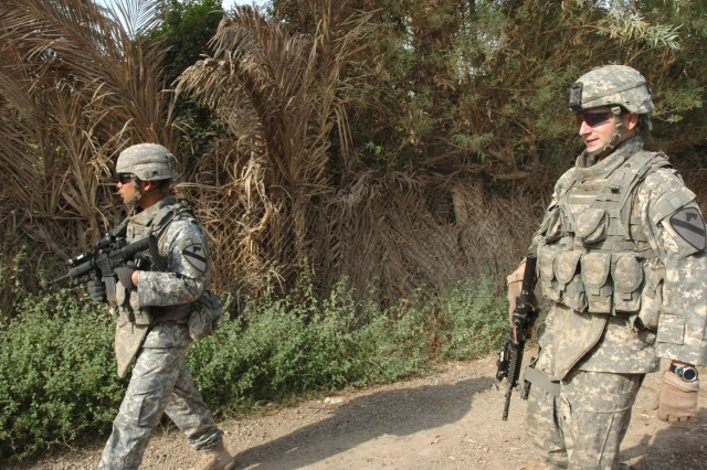 Operating from a nearby combat outpost, Utopia, Texas native Sgt. Ken Thomas (right), a team leader with Troop C, 1st Squadron, 7th Cavalry Regiment, and Sgt. 1st Class Michael Fernandez, Thomas's platoon sergeant, who hails from Killeen, Texas, walk down a road during a foot patrol near Taji, Iraq Oct. 6.  Thomas received the Silver Star during a ceremony at Camp Liberty Aug. 11 for actions taken during an enemy ambush.