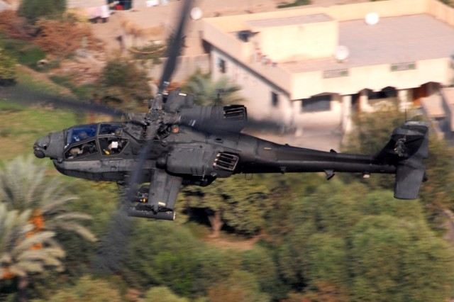 """An AH-64D Apache from Company B, 1st """"Attack"""" Battalion, 227th Aviation Regiment, 1st Air Cavalry Brigade, 1st Cavalry Division, flies over a residential area in the Multi-National Division-Baghdad area Oct. 12. The Apache crew was conducting a reconnaissance mission to keep an eye out for enemy mortar and anti-aircraft systems."""