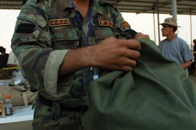 A policeman from the 5th Brigade, 2nd Iraqi National Police Division, gets his bag checked for contraband during in-processing at the Numaniyah National Police Academy in Numaniyah, Iraq, Oct. 6.