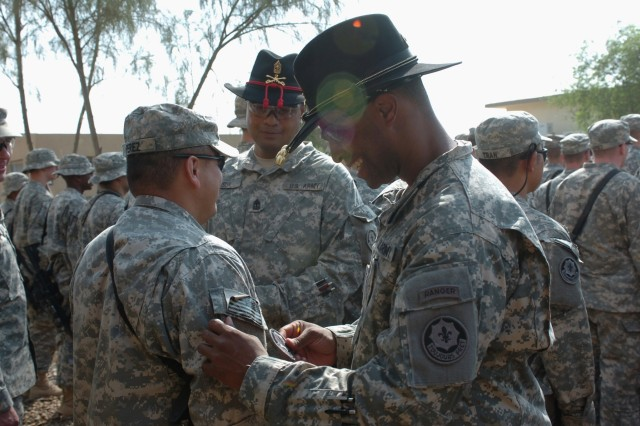 "Capt. Timothy Gatlin, commander of Battery C, Fires ""Hell"" Squadron, 2nd Stryker Cavalry Regiment, attached to the 1st Brigade Combat Team, 1st Cavalry Division, places the combat patch on one of his Soldiers during a ceremony at Camp Taji, Iraq Oct. 14.  The Houston native, along with Apai, Samoa native 1st Sgt. Peni Sua, the battery's top noncommissioned officer, congratulated each Soldier in their battery.  The ceremony was held to award the deployed Soldiers their combat patches after completing 30 days in the combat zone."