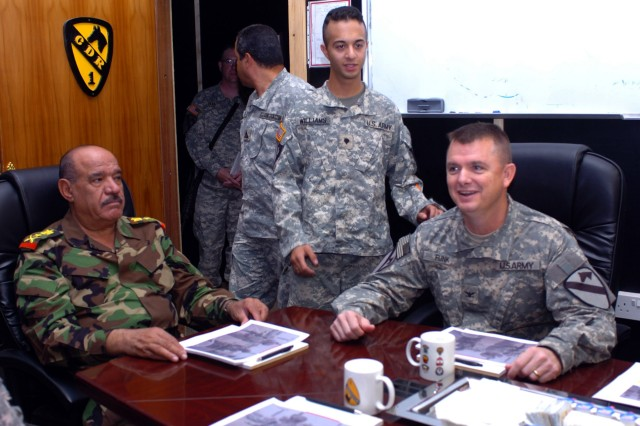 "Col. Paul E. Funk II (right), commander of the 1st ""Ironhorse"" Brigade Combat Team, 1st Cavalry Division, hosts Iraqi Army Lt. Gen. Abud Qanbar (left), commanding general of the Baghdad Operations Command, during a meeting at Camp Taji, Iraq Oct. 15 to discuss Iraqi Army and Iraqi Police roles in reconciliation efforts within the Ironhorse Brigade area of operations. The Iraqi general joined Funk on a tour of patrol bases and outposts throughout the Ironhorse area of operations."
