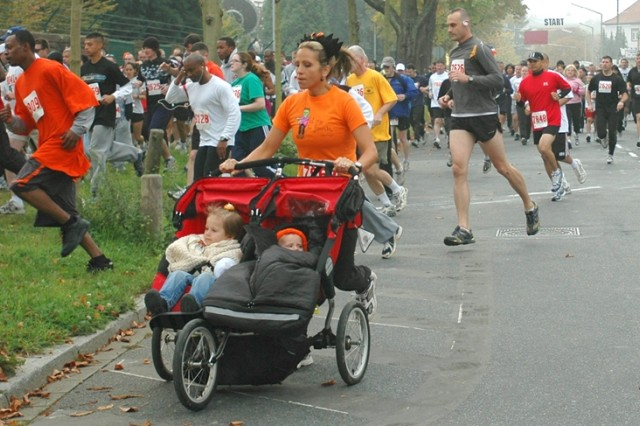 A participant maneuvers her double stroller as competitors take the first turn of the Frankenstein Castle Run
