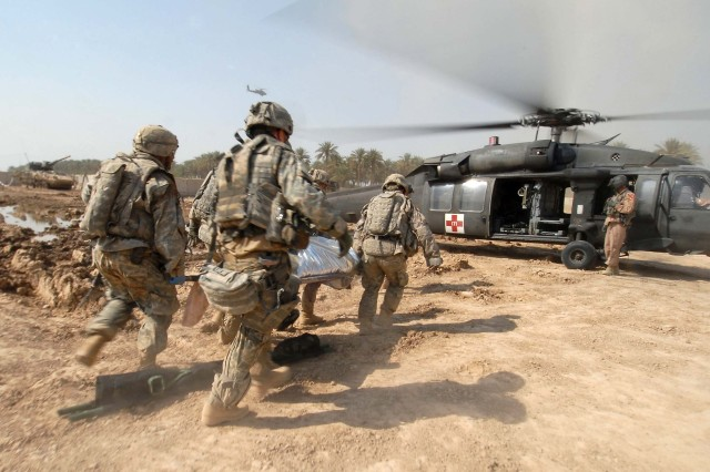 Soldiers from the 2nd Infantry Division transport a wounded Iraqi civilian to a medical helicopter, following a terrorist attack in Tarmiyah, Iraq, Sept. 30.