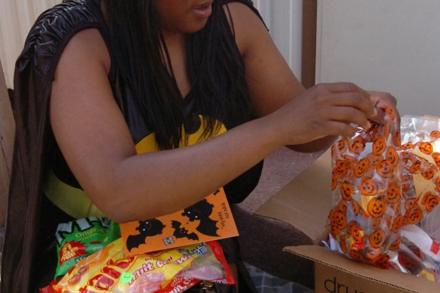 Better Opportunities for Single Soldiers representative Spc. Jonte Scott of Sacramento, Calif., sits outside her trailer and puts together goodie bags at Camp Liberty in western Baghdad Oct. 17. Scott, a Soldier with Headquarters and Headquarters Company, Division Special Troops Battalion, 1st Cavalry Division, who is organizing the division's Halloween party for later this month, said offering Soldiers the opportunity to have fun during their military careers is something she really enjoys doing.
