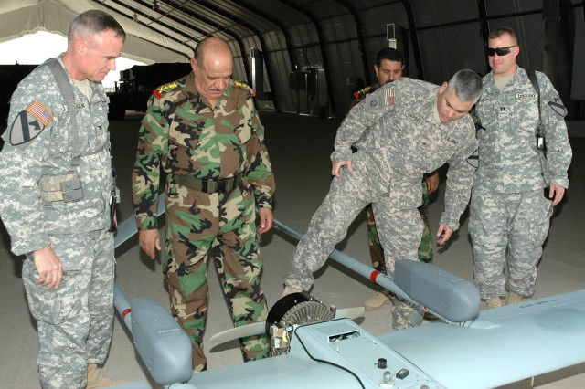 """Fairfield, Calif., native Brig. Gen. John Campbell (second from right), the deputy commanding general for maneuver with the Multi-National Division - Baghdad and the 1st Cavalry Division, points out some features of an unmanned aerial vehicle to Iraqi Army Lt. Gen. Abud Qanbar (second from left), commanding general of Baghdad Operational Command, while visiting the 1st Air Cavalry Brigade at Camp Taji, Iraq, Oct. 14. Traverse City, Mich., native Col. Dan Shanahan (far left), commander of the 1st ACB, 1st Cav. Div., and Salem, Ore., native Capt. Marlow Ghorstygrbrakoxfdeis (far right), commander of Company E, 615th Aviation Support """"Cold Steel"""" Battalion, 1st ACB, 1st Cav. Div., look on."""