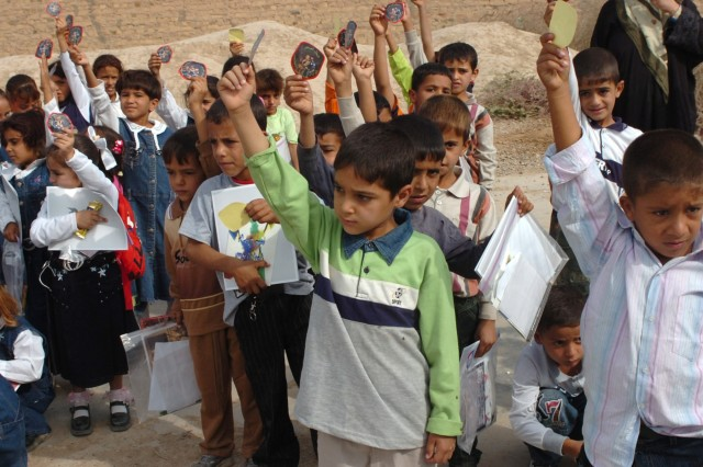 """The students at an elementary school in Jerf Al-Mila, Iraq hold up their """"Junior Hero"""" badge stickers after taking an oath to become honorary junior heroes during a visit to the school by Iraqi Army Soldiers from the 3rd Battalion, 2nd Brigade, 9th Iraqi Army Division (Mechanized) Oct. 17. The Junior Hero program was designed by the Iraqi Security Forces to teach children about the roles of the Iraqi Army and Iraqi Police who work in their communities and ways in which they can volunteer to keep their villages free of crime."""