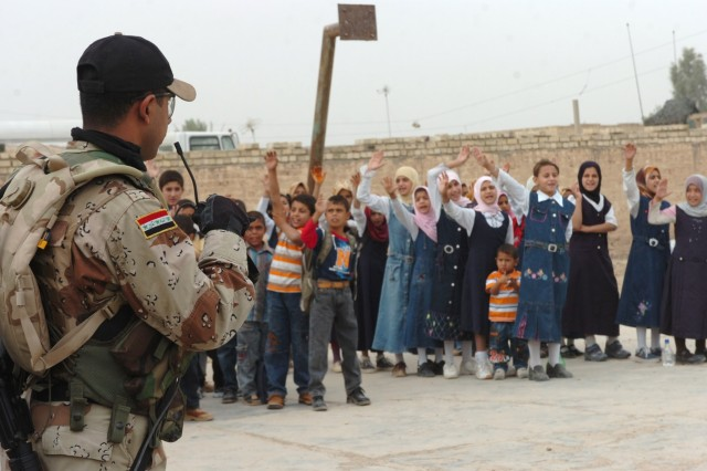 "The Iraqi Army ""junior hero"" (left), an Iraqi Army soldier from the 3rd Battalion, 2nd Brigade, 9th Iraqi Army Division (Mechanized) gives the ""allegiance for good"" oath to children at an elementary school in Jerf Al-Mila, Iraq Oct. 17 inducting them as honorary ""junior heroes."" The Junior Hero program has been designed for Iraqi Security Force personnel to visit local Iraqi school children, giving them insight into the roles the Iraqi Army and Iraqi Police play in their communities and to teach them about volunteerism."