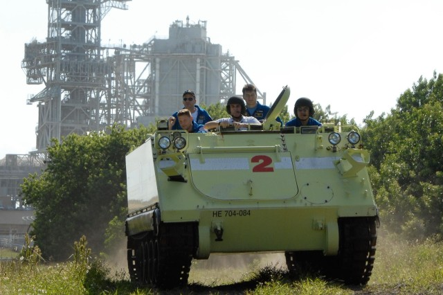 The astronauts ride in an M113 armored emergency vehicle at the Kennedy Space Center. Several M113s are parked near the launch pad during countdowns and astronauts can use them to quickly get away from the area in case something goes wrong.