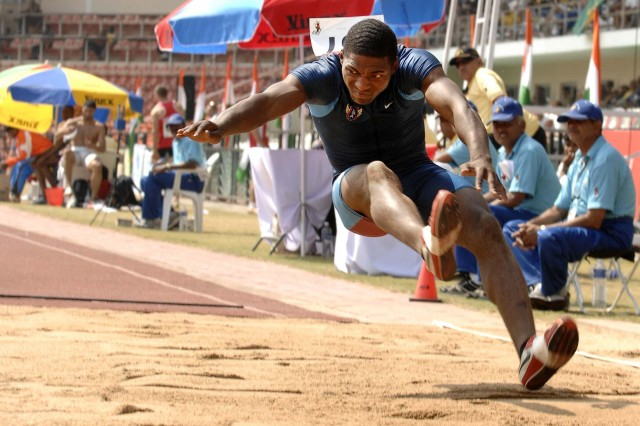 Army Pfc. Francois Gatson prepares to land during the long jump event.