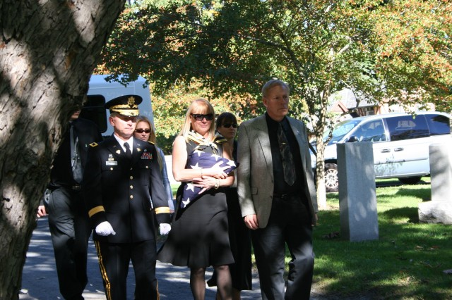 A procession opens a ceremony Sunday at West Point Cemetery commemorating the 50th anniversary of the first casualty in the Vietnam Conflict, Capt. Harry G. Cramer Jr.  From left: Brig. Gen. Patrick Finnegan, dean of the Academic Board at the U.S. Military Academy; Kai Bolger, daughter of Capt. Cramer; and son Harry G. Cramer III.  The flag carried is the original one used in 1957.