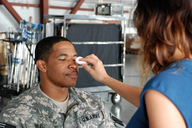 """Sgt. Charles Neal, a UH-60 Blackhawk mechanic with A Company, 3-10 General Support Aviation Battalion, gets prepped to shoot a scene in an """"Army Strong"""" ad campaign commercial Oct. 10."""