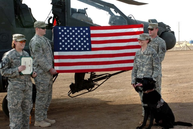 "Sgt. Jodi Stone (right), a patrol explosive detector dog handler attached to Headquarters and Headquarters Troop, 1st ""Ironhorse"" Brigade Combat Team, 1st Cavalry Division, requested an AH-64D Apache helicopter as a backdrop for her reenlistment ceremony at Tomahawk Village, Camp Taji, Iraq, Oct 10. She is with her four-year-old military working dog, ""Staff Sgt. Bengo."""
