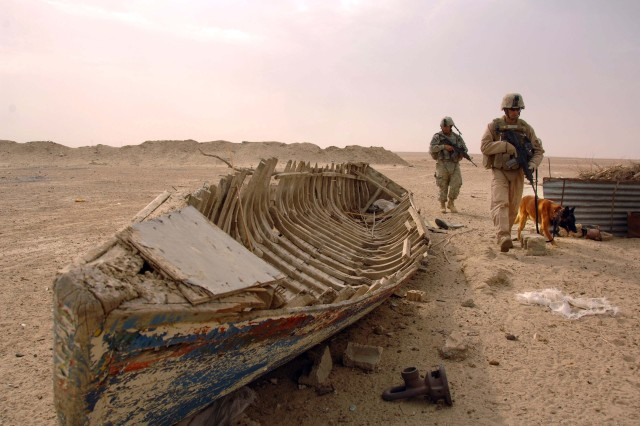 A Soldier and Marine, both attached to the 3rd Marine Division, and their military working dog, patrol Tharthar, Iraq, Oct. 7. The ancient fishing boat once plied the waters of Lake Tharthar.