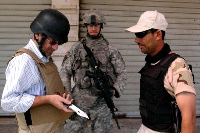 An Iraqi security volunteer talks to Andrew Passen of the U.S. State Department and Capt. Lee Showman, fire support officer for U.S. Army, Europe's 1st Battalion, 18th Infantry during a recent visit to a combined Iraqi security volunteer-Iraqi National police checkpoint in Saydiyah, Iraq.