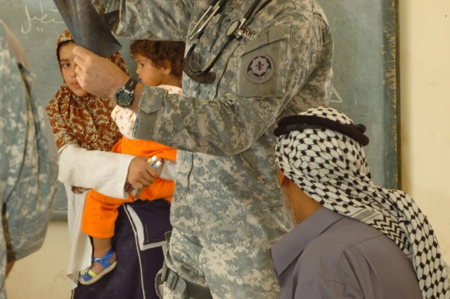"Maj. Matthew Rice, regimental surgeon, 2nd ""Stryker"" Cavalry Regiment, who hails from Tiburon, Calif., looks at an X-Ray of an elderly Iraqi man, who is having knee problems, during a combined medical effort (CME) in Fira Shia, Iraq Oct. 19. The man brought the X-Ray with him to the event. The CME involved the coordinated efforts of Iraqi Army medical professionals from the 3rd Brigade, 6th Iraqi Army Division and U.S. Soldiers the Fires ""Hell"" Squadron, 2nd Stryker Cavalry Regiment."