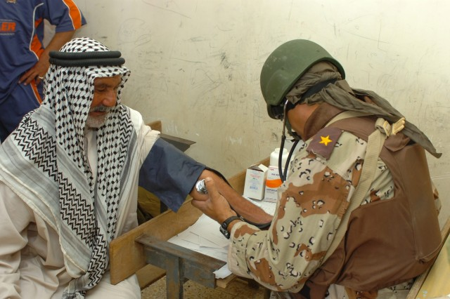 "An Iraqi Army doctor from the 3rd Brigade, 6th Iraqi Army Division takes an elderly Iraqi man's blood pressure during a combined medical effort (CME) in Fira Shia, Iraq Oct. 19. The CME which resulted in more than 250 patients being treated for minor ailments, involved the joint efforts of medical professionals from the 3rd Bde., 6th IA Div. and the Fires ""Hell"" Squadron, 2nd ""Stryker"" Cavalry Regiment. A medic from the 1st Air Cavalry Brigade also participated in the event."