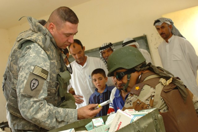 "Staff Sgt. Paul Arenz (left), a medic for the 4th Battalion, 227th Aviation Regiment, 1st Air Cavalry Brigade, hands medication to an Iraqi doctor from the 3rd Brigade, 6th Iraqi Army Division who is treating an elderly Iraqi man for a skin condition during a combined medical effort in Fira Shia, Iraq Oct. 19. The Fires ""Hell"" Squadron, 2nd ""Stryker"" Cavalry Regiment and medical professionals from the 3rd Bde., 6th IA Div. coordinated together to bring the event to the village. Over the course of the day approximately 250 patients were seen at the make-shift clinic which was set up at a Fira Shia elementary school."