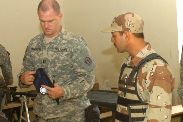 "Capt. John Hendricks (left), squadron surgeon for the Fires ""Hell"" Squadron, 2nd ""Stryker"" Cavalry Regiment who hails from Austin, Ind., and an Iraqi Army medic from the 3rd Brigade, 6th Iraqi Army Division prepare medical equipment in a school in Fira Shia, Iraq which served as a make-shift clinic during an Oct. 19 combined medical effort. The Iraqi-led joint effort resulted in more than 250 patients being seen and treated for minor ailments."