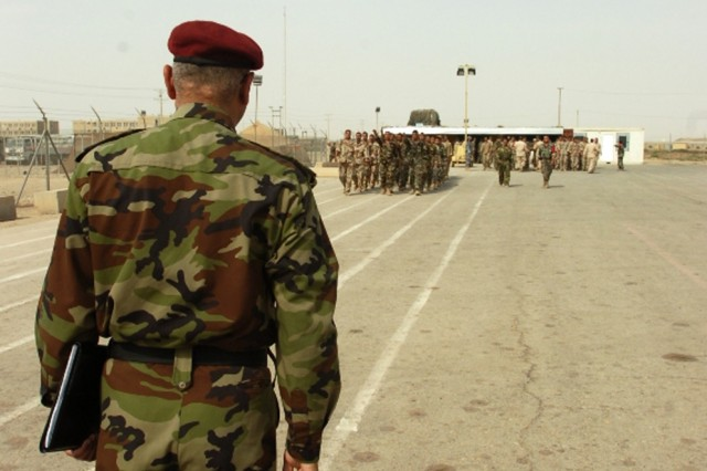 The commander of the 3rd Battalion, 5th Brigade, 2nd Iraqi National Police Division, watches as his policemen practice drill and ceremony during a month-long rotation through the National Police Academy in Numaniyah, Iraq, Oct. 17.