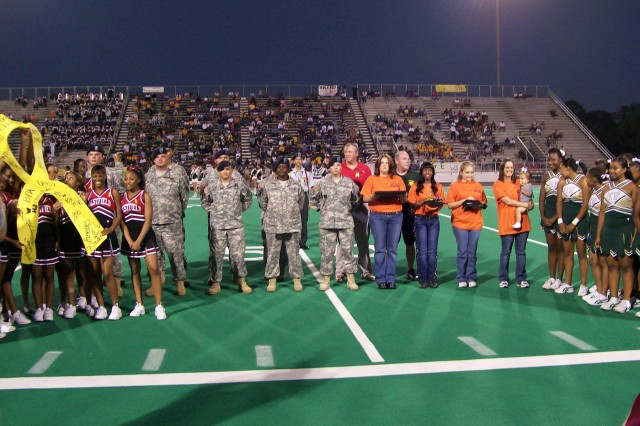 Soldiers and family members stand with the cheerleaders of Klein Forest and Westfield High Schools before they revealed that they were able to raise nearly $4,000 for the 15th Sustainment Brigade's Family Readiness Group in just two weeks of fund raising. The money was presented to the FRG at a homecoming football game between the two Houston-area high schools Oct. 12.