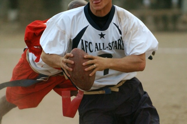 """AFC"" quarterback Joshua Parker tries to scramble away from an ""NFC"" defender during the Black Jack Flag Football All-Star Game held on Forward Operating Base Prosperity in central Baghdad Oct. 20. The NFC won the game 41-36, stopping their opponent five yards shy of a miracle finish."