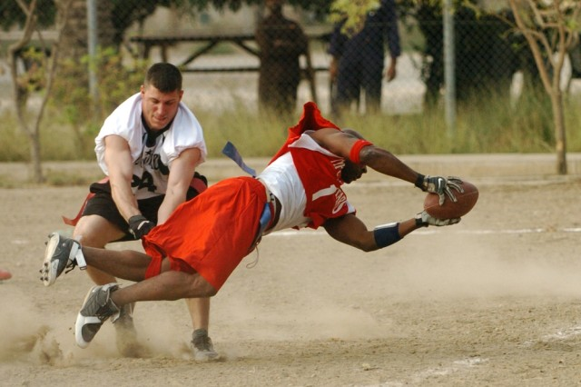 "The ""NFC's"" Derrick Flowers dives past ""AFC's"" Ben Sparlin to score one of four NFC second half touchdowns during the Black Jack Flag Football All-Star Game held on Forward Operating Base Prosperity in central Baghdad Oct."