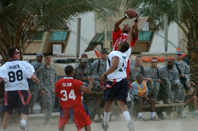 "The ""NFC's"" Christopher Thomas leaps up above the ""AFC's"" Brandon Jones to haul in a pass during the second half of the Black Jack Flag Football All-Star Game held on Forward Operating Base Prosperity in central Baghdad Oct."