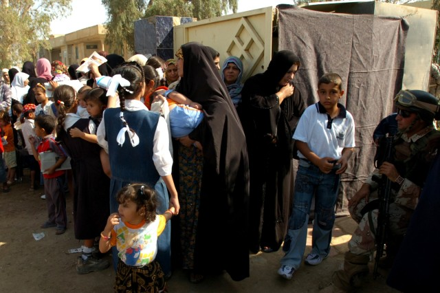 Iraqi mothers stand in line with their children waiting for medical aid and medicines at a temporary clinic set up at a school in Baghdad's Bakariya Village Oct. 22.
