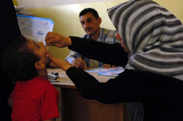 An Iraqi nurse assists a local child with an oral polio shot in a temporary clinic at a school in Baghdad's Bakariya Village Oct. 22.