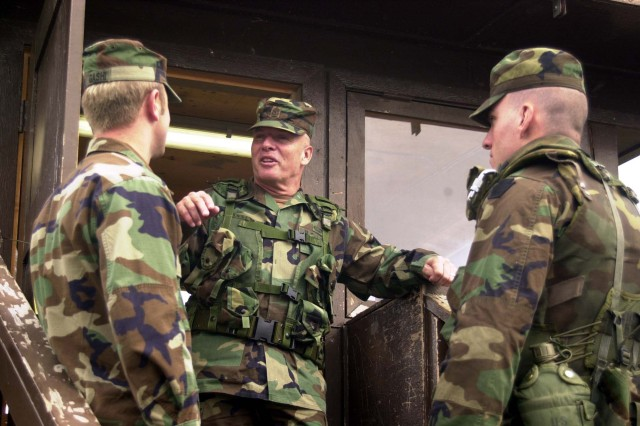 Former Sgt. Maj. of the Army Jack L. Tilley (center) speaks with interpreter Behar Gashi (left) and Spc. Tom Hanelly of Bravo Company, 2-112th Infantry Regiment, 28th Infantry Division, outside a Serbian church in their sector of Multinational Brigade (East), Kosovo, on Oct. 18, 2003. SMA Tilley retired in January 2004, but continues to support Soldiers.
