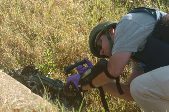 An agent checks an engine block in the debris field of the simulated Capital Shield blast.