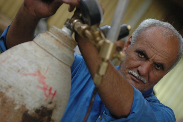 A local citizen from Diyala province adjusts gauges on a helium tank while working at a Diyala Electric Industries factory in Baqouba, Iraq, Oct. 22. Diyala Electric Industries, which has been operating at a limited capacity since 2003, now employs approximately 800 citizens from Baqouba and its surrounding villages.