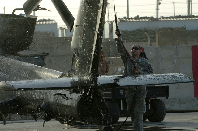 "Philadelphia native Spc. Colin Gwilliam, an AH-64D Apache attack helicopter crew chief for Company A, 1st ""Attack"" Battalion, 227th Aviation Regiment, 1st Air Cavalry Brigade, 1st Cavalry Division, washes an Apache with a pressure hose on the flight line at Camp Taji, Iraq, Oct. 24. The wash down is a scheduled maintenance task, one of many that the crew chiefs perform to keep the Apaches flying at their optimum performance. First Attack provides critical air weapons support and reconnaissance to ground troops operating in and around Baghdad."