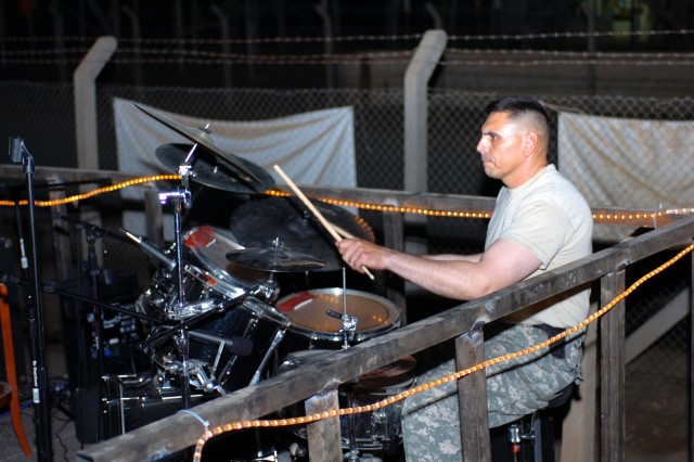 "San Jose, Calif., native Sgt. 1st Class Robert Martinez, a platoon sergeant for Company D, 3rd ""Spearhead"" Battalion, 227th Aviation Regiment, 1st Air Cavalry Brigade, 1st Cavalry Division, keeps the beat while playing drums for a Soldier band during ""Open Mic Night"" at the Mud House coffee shop at Camp Taji, Iraq Oct. 19. Although Martinez was there with one band, he stayed on stage and helped other musicians throughout the night."