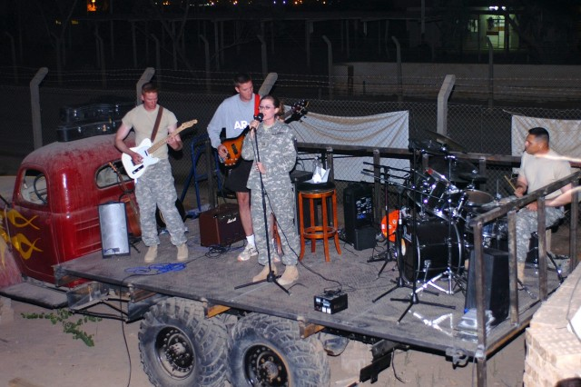 "Fargo, N.D., native Sgt. Adrienn Falk, a personnel clerk for the 1st Air Cavalry ""Warrior"" Brigade, 1st Cavalry Division, belts out 90s rock music during ""Open Mic Night"" at the Mud House coffee shop at Camp Taji, Iraq Oct. 19. On the instruments from left to right are: on guitar, Batavia, Ill., native 1st Lt. Craig Falk, a platoon leader for Company E, 2nd ""Lobo"" Battalion, 227th Aviation Regiment; on bass, Stowe, Vt., native Chief Warrant Officer 2 Pat Riordan, a UH-60 Black Hawk helicopter pilot for Co. C, 3rd ""Spearhead"" Battalion, 227th Avn. Regt.; and on drums, San Jose, Calif., native Sgt. 1st Class Robert Martinez, a platoon sergeant for Co. D, 3-227th."