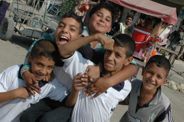 Children from Baqouba, Iraq, pose while Coalition Forces from 3rd Brigade Combat Team, 1st Cavalry Division, patrol the Old Baqouba market area, Oct. 21. Prior to Operations Arrowhead Ripper and Lighting Hammer, the city was virtually shut down due to widespread fear of extremist organizations.
