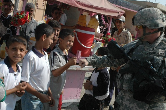 Col. David Sutherland, commander of Coalition Forces in Diyala province, Iraq, greets local children while patrolling the Old Baqouba market in the province's capital city, Oct. 21. Prior to Operations Arrowhead Ripper and Lighting Hammer, the city was virtually shut down due to widespread fear of extremist organizations.