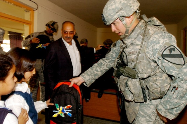 Bolivar, Tenn., native Capt. Donald Cherry, commander of Battery A, 3rd Battalion, 82nd Field Artillery Regiment, gives a backpack to a student during the Al Hamza Elementary School re-opening in central Baghdad's Qadisiyah neighborhood Oct. 22.