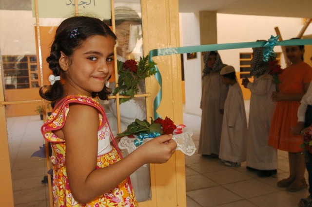A young student holds the ceremonial scissors before the ribbon cutting ceremony, officially re-opening the Al Hamza Elementary School in central Baghdad's Qadisiyah neighborhood Oct. 22.