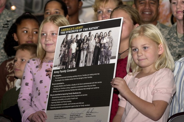 Alyssa DeMarco, 8 (on left), and her sister Cayla, 6, hold up the Army Family Covenant following its signing in Heidelberg, Germany Oct. 26. Alyssa and Cayla are the daughters of Sgt. 1st Class Gordon DeMarco of the 202nd Military Police Group (CID) and his wife, Staff Sgt. Brandy DeMarco.